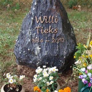 Schwarzer Grabstein aus Granit mit Blumenschmuck