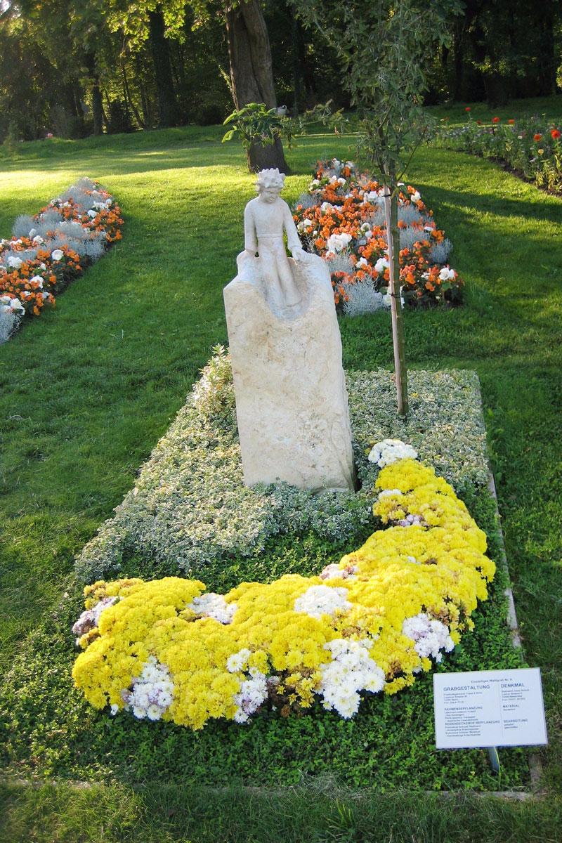 Skulptur des kleinen Prinzen aus weißem Sandstein mit Blumenbepflanzung