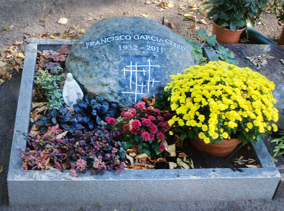 Dunkler Grabstein mit Blumenschmuck
