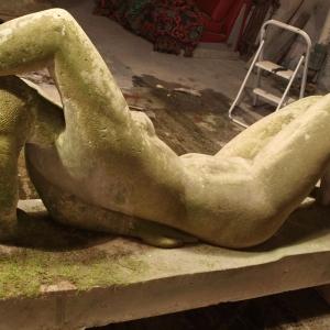 Skulptur einer liegenden Frau aus Sandstein vor der Restaurierung überzogen mit Moos Rückenansicht