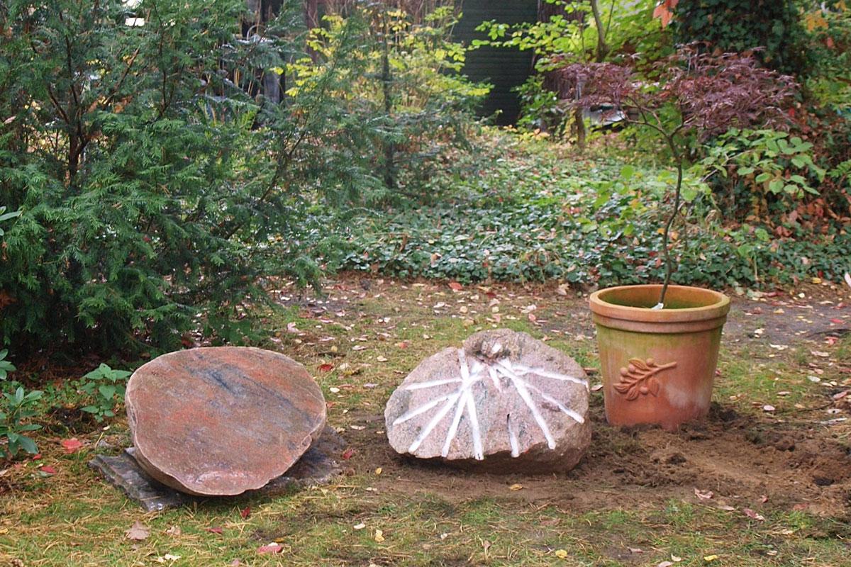 Grabstein in Form einer Elipse aus Findling in Garten