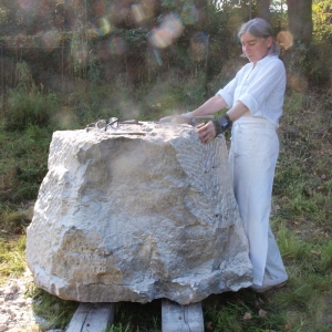 Bildhauerin Emerita Pansowova draußen vor einem großen Stein