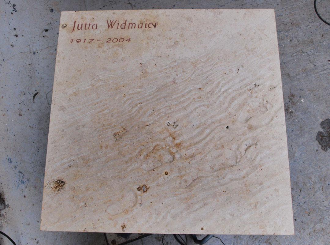 Grabstein in Form einer Platte aus weißem Kalkstein mit Fußspuren