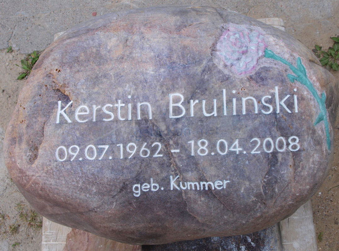 Grabstein in Form eines rötlichen Findlings mit Motiv Nelke