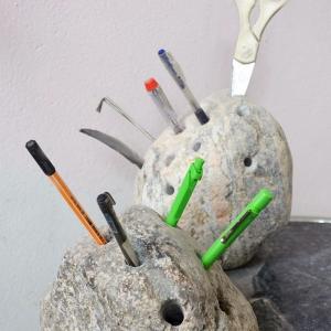 Polierter Stein mit Löchern und vielen Stiften darin