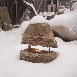 Lampe aus Findling mit brennender Kerze draußen im Schnee