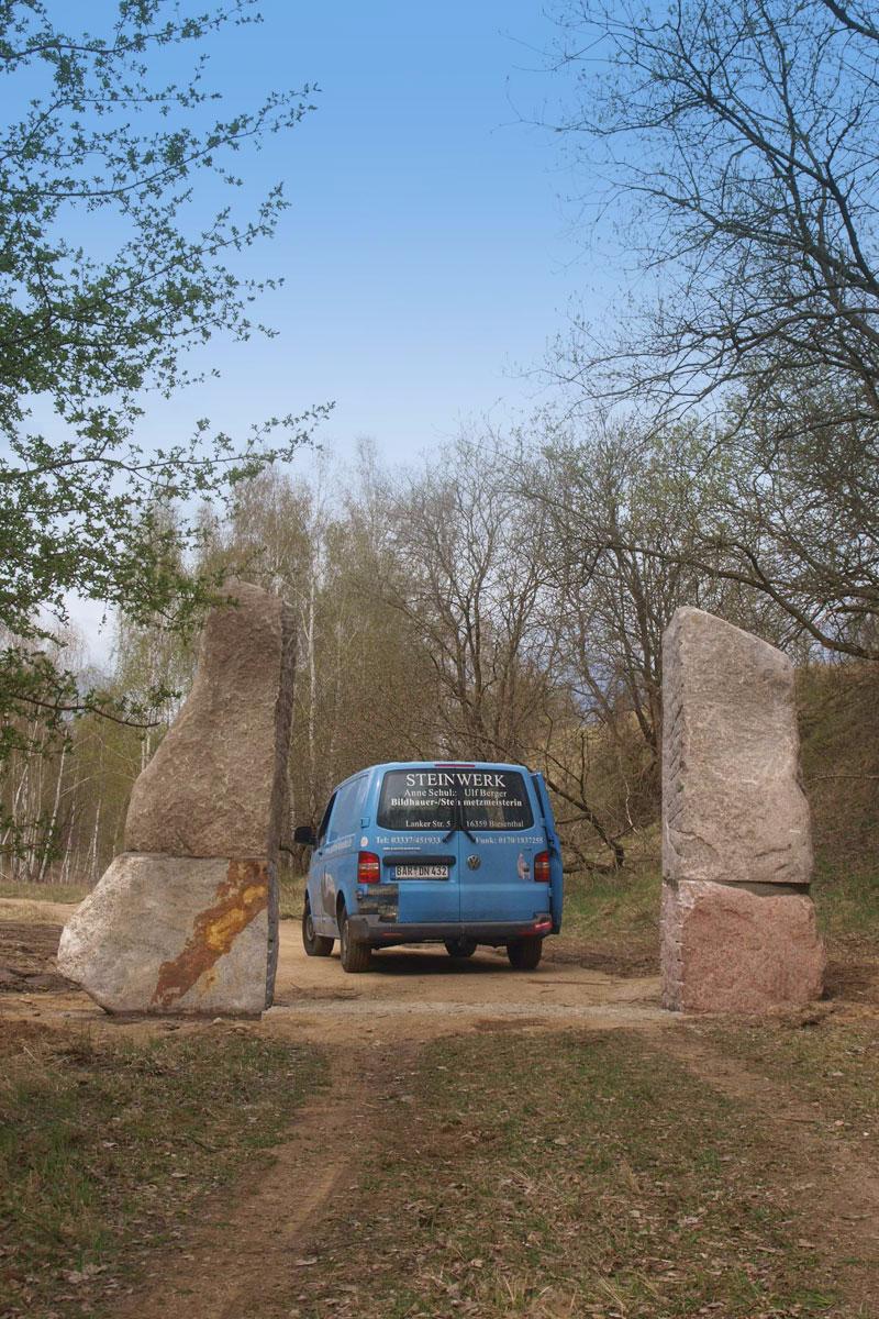 Tor auf freiem Feld im Geopark aus zwei hohen Steinen mit blauem Bus