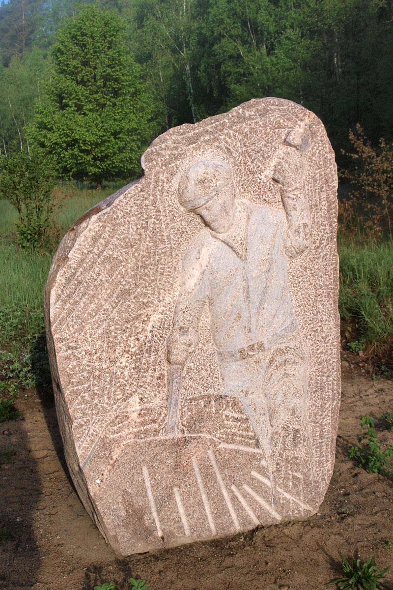 Gehauener Stein auf freiem Feld mit Motiv Steinhauer der Findlinge zum Mauern oder als Pflastersteine spaltet