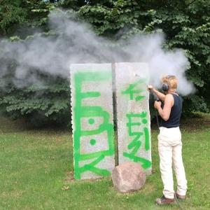 Anne Schulz im freien bei der Entfernung von Graffiti auf Skulptur