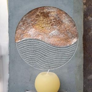 Steinmotiv mit Welle und gelber Kerze davor