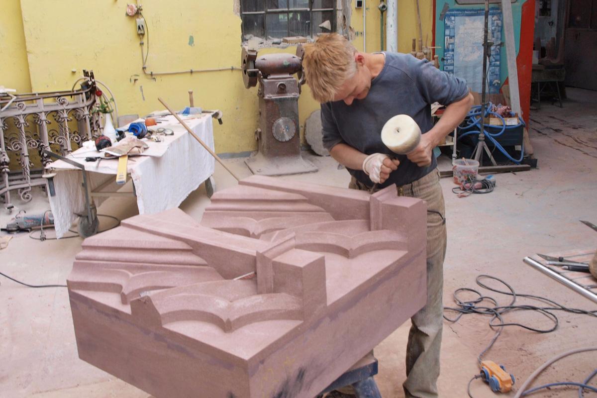 Anne Schulz in der Werkstatt an der Arbeit zu Maßwerk aus rotem Sandstein