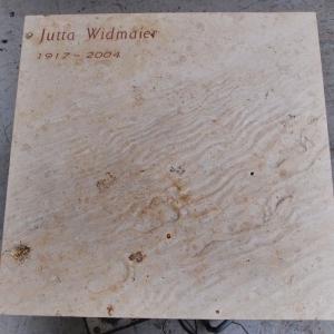 Grabstein aus hellem Kalkstein als Platte mit Relief in Form von Fußspuren