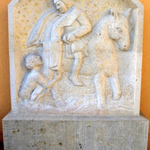 Relief von St. Martin auf dem Pferd mit Bettler vor oranger Wand