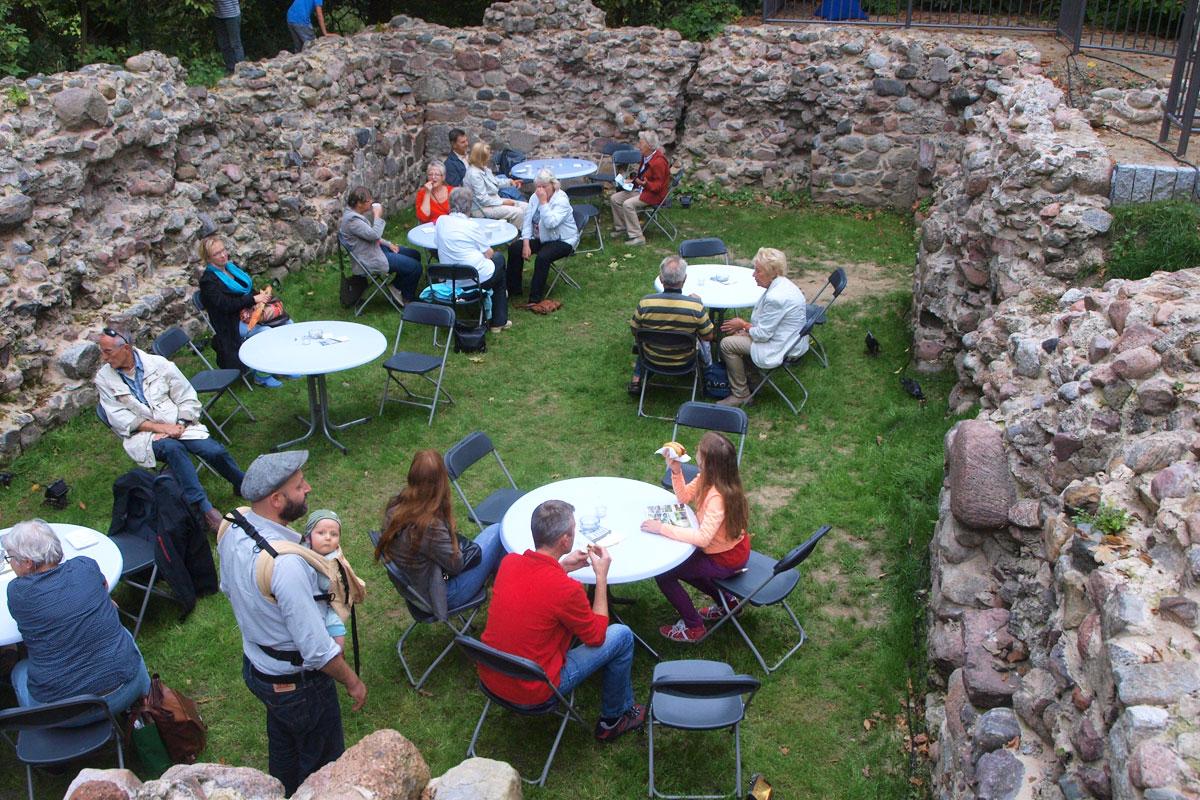 Blick auf restaurierte Burgruine bei der Einweihung mit Menschen an Tischen