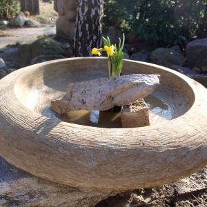 Große runde Schale aus hellem Sandstein auf freiem Gelände