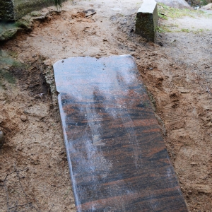 Rutsche aus rötlicher, regennasser Steinplatte auf Spielplatz