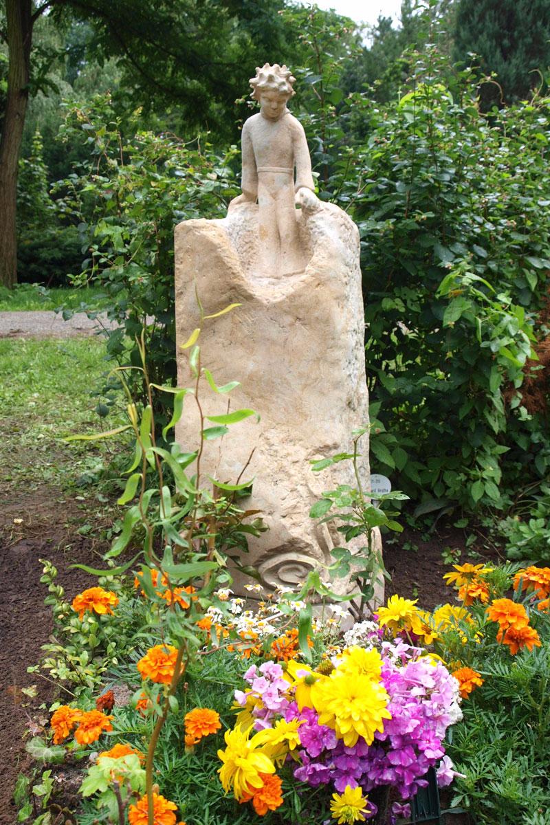Grabstein als Stele aus hellem Sandstein in Form des kleinen Prinzen mit Blumenschmuck