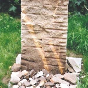 Grabstein als Stele aus rötlichem Porphyrtuff in Form eines Dreiecks