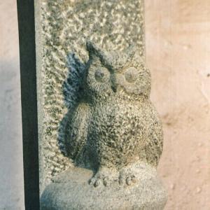 Skulptur als Stele aus grauem Quarzit in Form einer Eule