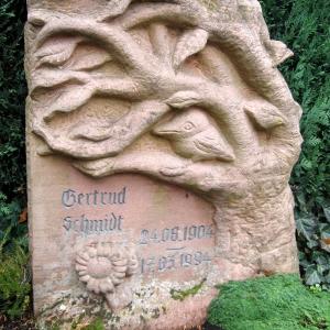 Grabstein als Stele aus rötlichem Sandstein in Form eines Baumes mit Vogel