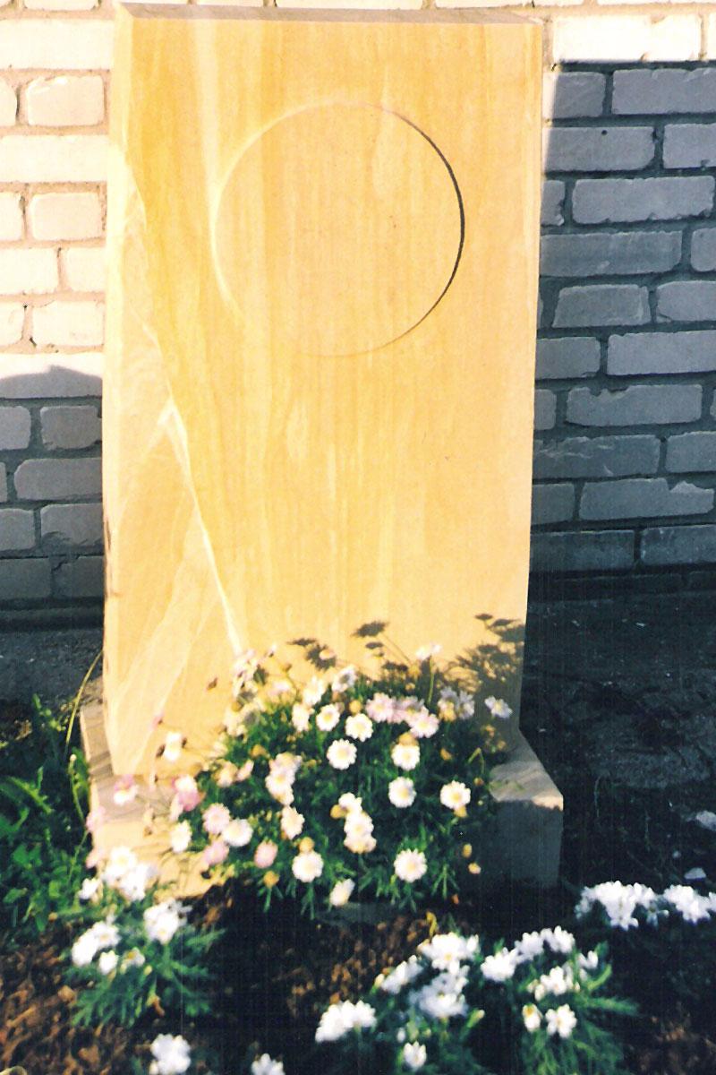 Grabstein als Stele aus gelblichem Sandstein mit Sonne als Scheibe