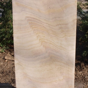 Grabstein als Stele aus hellem Sandstein mit Kopf in Wellenform