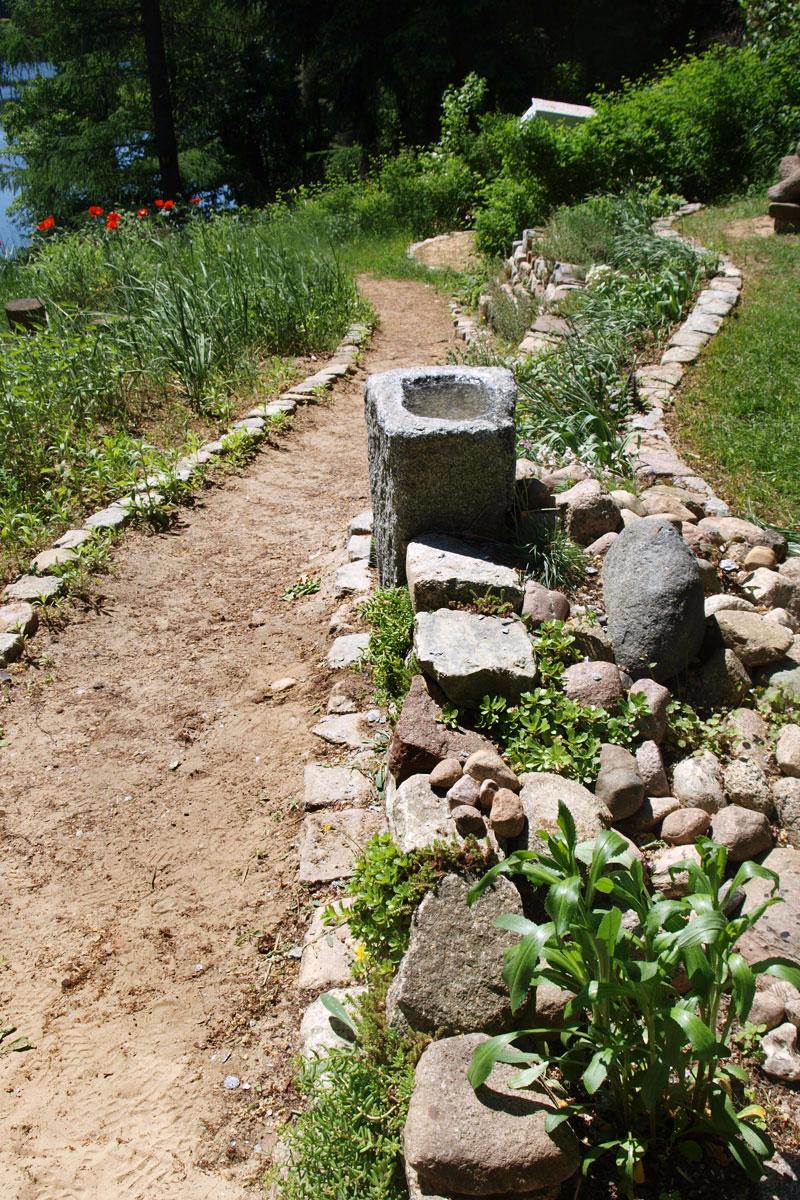 Wasserbecken aus Granit in Form einer rechteckigen Stele in einem Garten
