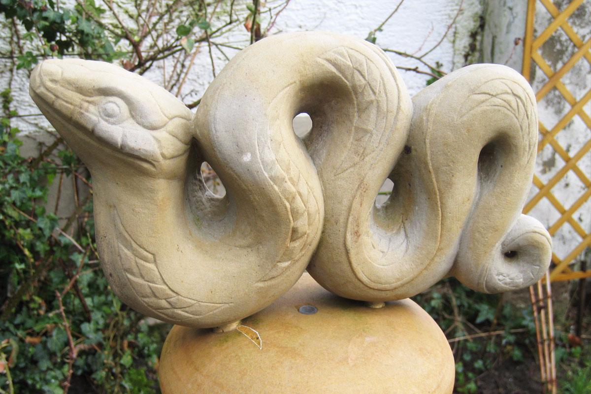 Quellstele aus hellem Sandstein in Form einer Schlange