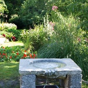 Brunnen aus dunklem Granit in Form eines Tisches in einem Garten