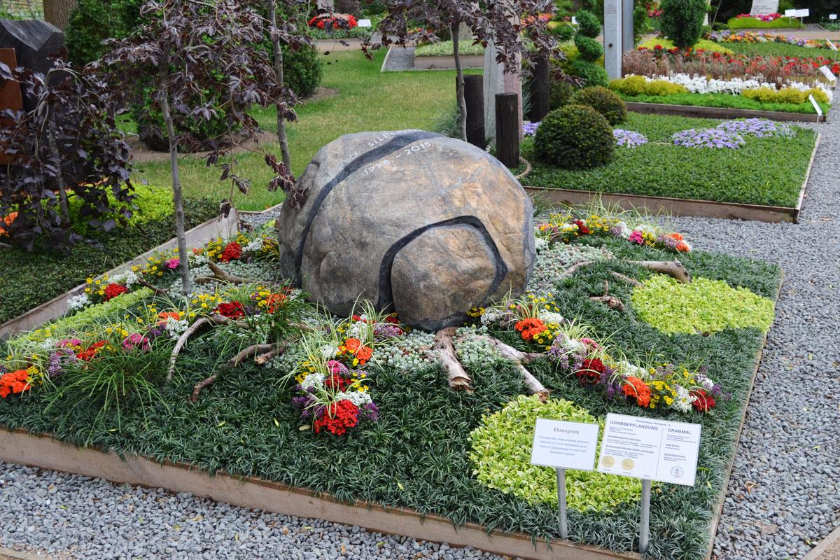 Grabstein in Form einer abgewickelten Zitronenschale in mitten bunter Bepflanzung auf Bundesgartenschau