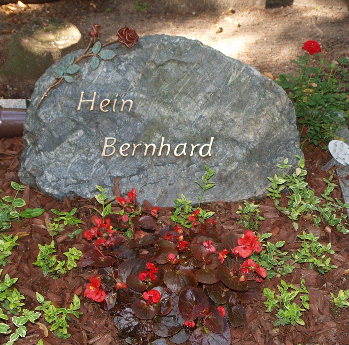 Rose und Bronzebuchstaben auf antrazithfarbenem Findling